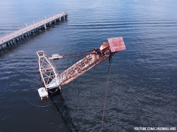 Abandoned crane and barge sunken into the river
