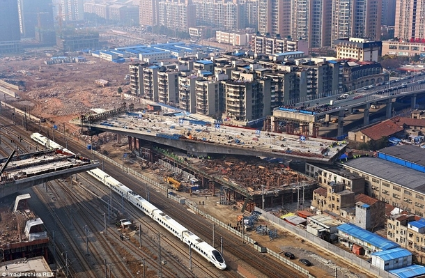 ton bridge section built next to train tracks and slowly rotating into place - Wuhan City China