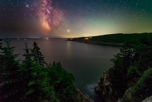 A humid hazy night and a setting Milky Way overlooking Hunters Beach in Acadia National Park Maine