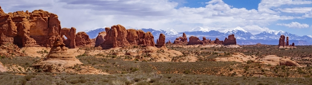 A little of everything that makes up Utah mountains snow sagebrush and red rock Arches National Park