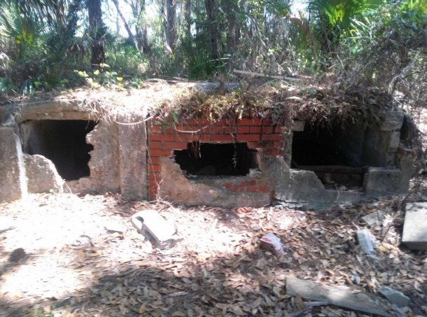 Abandoned cemetery in Florida with broken open vaults A casket is visible in the far right vault only a few bones are present and one of the casket lids has been ripped off