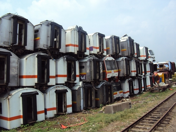 Abandoned Indonesian commuter trains stacked high on a field near Purwakarta Station Photo by cc