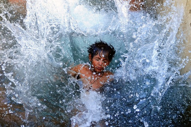 An Indian kid cools off in a watering hole on a hot day in Allahabad