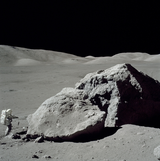 Apollo  astronaut Harrison Schmitt standing next to a boulder during the third EVA