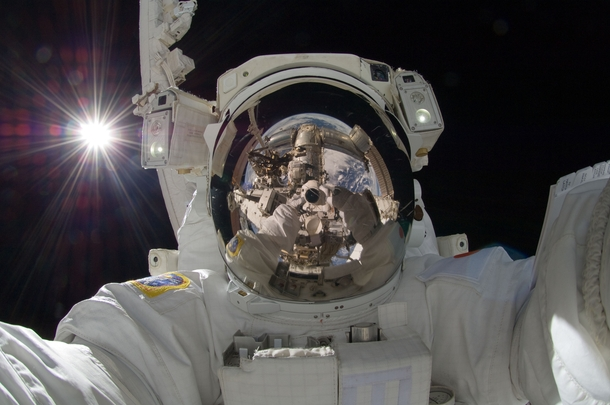 Astronaut Aki Hoshide Expedition  flight engineer uses a digital still camera to expose a photo of his helmet visor during the missions third session of EVA  xpost rtechnologyporn