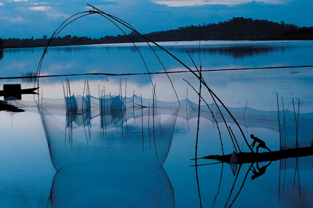 At twilight on floodwaters from the Brahmaputra River a fisherman maneuvers a net on bamboo poles EPACorbis