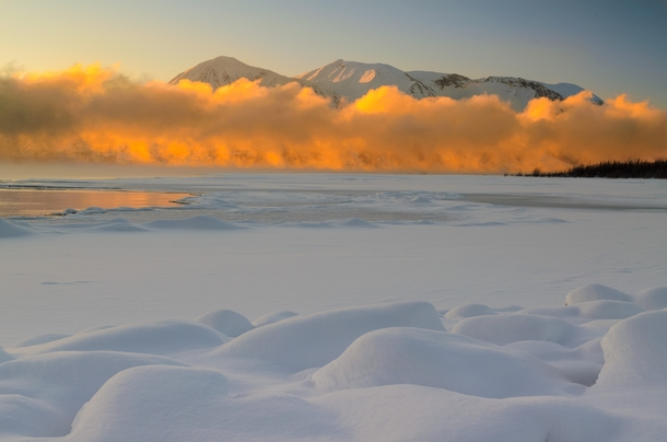 British Columbia Canada This large fog bank was traveling down the length of Atlin Lake It was mostly in the shade until the warm rays of a setting sun hit it from behind It felt like someone had just tripped a light switch writes photographer Christian B