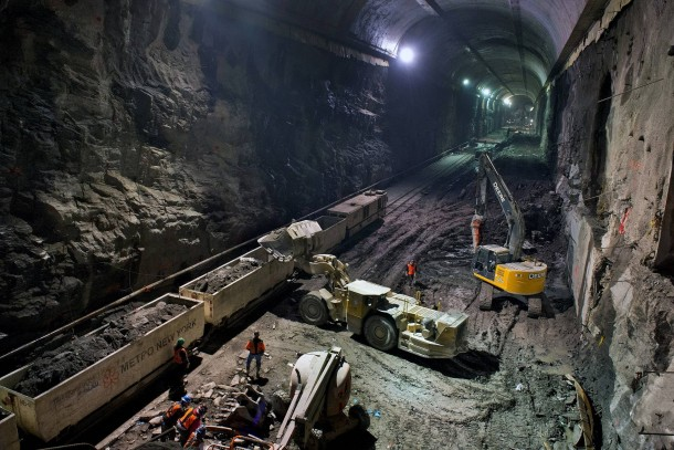 Far beneath the bustling streets of Manhattan and out of sight for the majority of New York Citys  million residents the largest transportation project in the country is churning away day and night hollowing out granite to create six miles of new tunnels