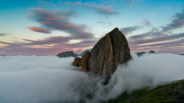 Fog at the base of a mountain near Mefjordvr Norway  photo by Andre Ermolaev