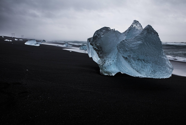 Ice chunks wash up on the shore of a black sand beach at Jokulsarlon Iceland