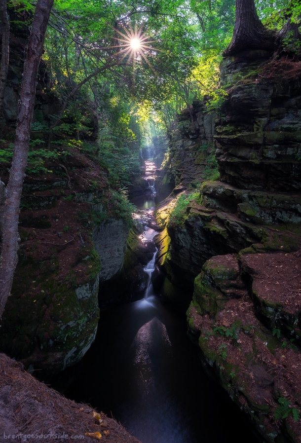 Light bursts through the trees onto the waterfalls of Skillet Creek in Pewits Nest Wisconsin