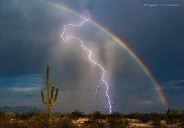 Lightning strikes in front of a rainbow in a southern Arizona desert