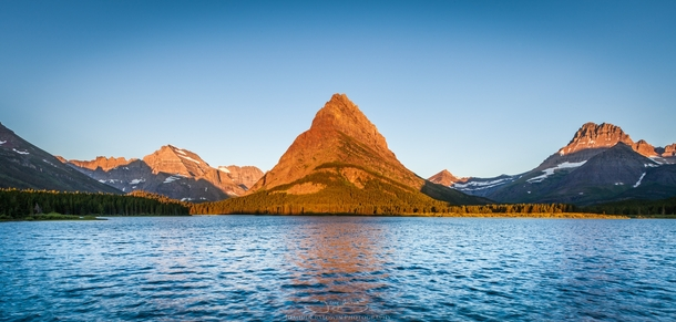mount grinnell at sunrise reflected on swiftcurrent lake glacier