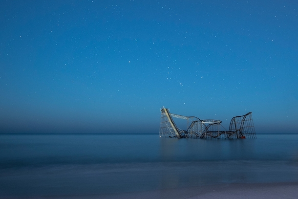 Starry skies over the Jet Star Roller Coaster sitting in the Atlantic Ocean by Jack Fusco