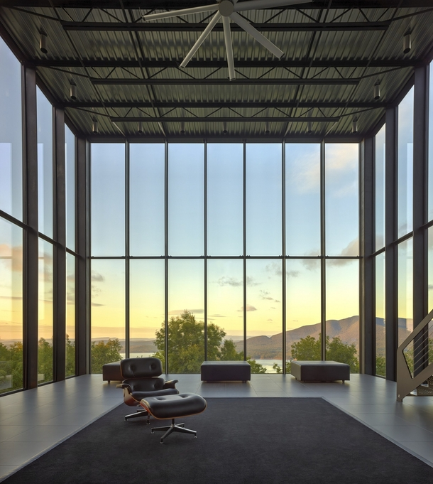 Steel-framed living room of Shokan House with views across treetops to the Ashokan reservoir just below the summit of a Catskill mountain Ulster County New York