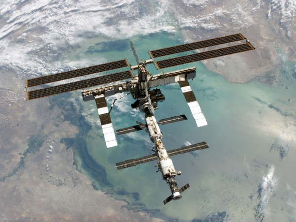 The ISS after being visited and resupplied by space shuttle Discovery orbiting above the Caspian Sea