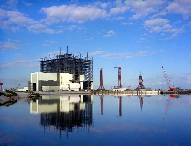 The Vehicle Assembly Building under construction in  at the Kennedy Space Center Florida It was first used to assemble the Saturn V rockets for the Apollo Program When completed it was the largest building in the world by volume and still holds the  spot