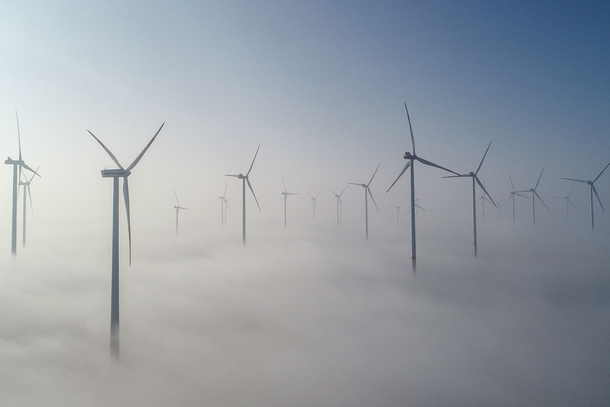 Turbines poke above the morning fog at a wind farm in Jacobsdorf Germany on Feb