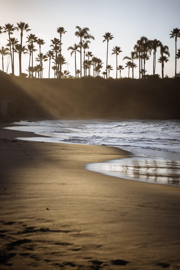 Woke up at  AM to get to the beach at sunrise Absolutely nobody on the sand and caught these magnificent rays peaking over the cliff Laguna Beach California