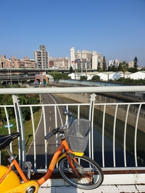 Public bike share bicycle on a path over a flood gate overlooking a canal leading to the Keelong river with walls to withstand flooding another bike path and a two-layer urban freeway in the background Taipei Taiwan