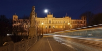 The Maximilianeum seat of the Bavarian State Legislature at night with light trails created by a passing streetcar