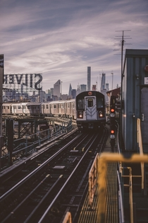 train meandering in front of the Manhattan Skyline - Queens NYC