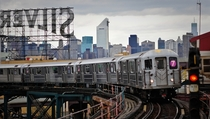 train moving into Queensboro Plaza with the Manhattan skyline in the background