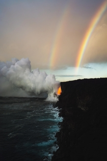 A beautiful double rainbow forms over a massive lava spout in Hawaii
