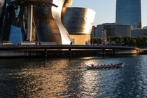 A boat floating past Gehrys Guggenheim Museum in Bilbao Spain