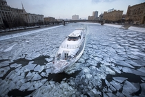 A boat navigates the icy river Moskva or Moscow River in Moscow Russia Alexander Zemlianichenko