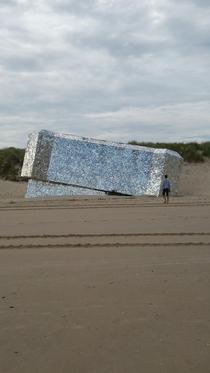 A bunker on the beachfront of Normandy covered in shards of mirrors
