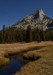A calm stream leading to a jagged spire of granite Cathedral Peak Yosemite National Park CA  seanaimages