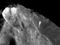 A closeup of Saturns small moon named Phoebe recorded by NASAs Cassini orbiter the white stuff in the craters is believed to be ice
