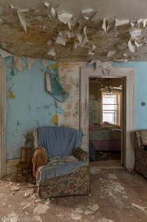 A cozy chair surrounded by peeling paint and decay in an abandoned house in Ontario Canada c