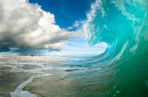 A crashing wave on the beach Photo by Chris Burkard