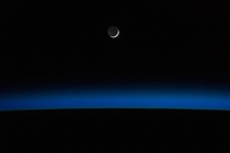 A crescent moon and Earths horizon are featured in this nighttime image photographed by an Expedition  crew member on the International Space Station May