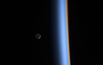 A crescent moon and the earths atmosphere taken from the ISS Feb st