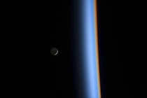 A crescent moon rises over the cusp of the Earths atmosphere