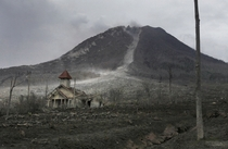 A damaged church is dwarfed by Mount Sinabung in the abandoned village of Simacem North Sumatra Indonesia Binsar Bakkara
