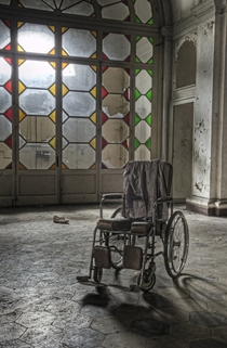 A decaying wheelchair sits in an abandoned asylum in Italy By Dan Raven on Flickr