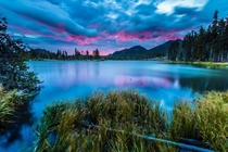 A dramatic and vibrant sunrise in Sprague Lake in Rocky Mountain National Park x