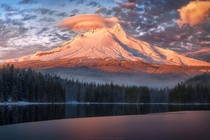 A freshly snowed Mt Hood holds on to the final moments of sunlight as fog rolls in at Trillium Lake Oregon