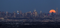 A full moon rises behind the New York City skyline -