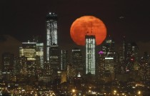 A full moon rises over the skyline of Lower Manhattan