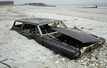 A half-buried early-s Dodge Polara station wagon on the beach in Queens New York  Photograph by Andy Blair