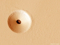 A Hole in Mars The hole about  meters across was discovered by chance in  on images of the dusty slopes of Mars Pavonis Mons volcano taken by theHiRISE instrument aboard the robotic Mars Reconnaissance Orbiter currently circling Mars