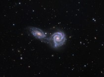 A hundred million light years away two spiral galaxies are locked in an embrace that may end with them merging a dance spread across a hundred thousand light years and tens of million years Arp