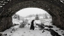 A hunter shelters under a bridge during a snow storm in the Glens of Antrim near Cargan Northern Ireland