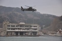 A Kawasaki OH- Ninja scout helicopter flies over the ruins of Funakoshi Bay in the wake of the tsunami th April