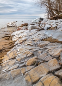 A layer of ice on the yellow sandstone by lake Vttern in Sweden